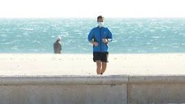 Un corredor haciendo deporte por la playa