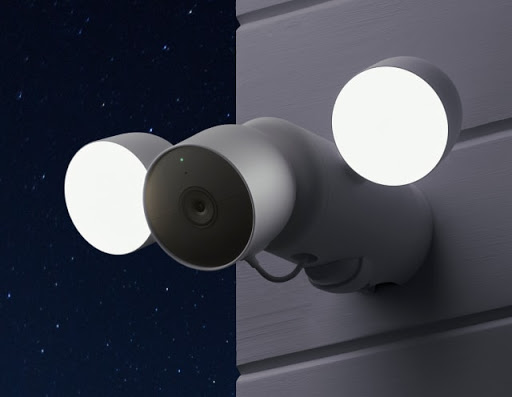 Nest Cam with the floodlight is on the side of a home and the lights are shining bright at night.