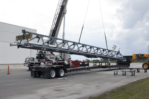 The umbilical swing arm for Exploration Flight Test 1 arrives and is being lifted by crane from its transporter.