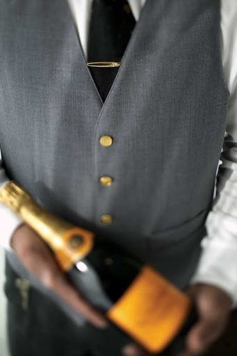 A butler handles a bottle of Champagne on a Regent Seven Seas cruise.