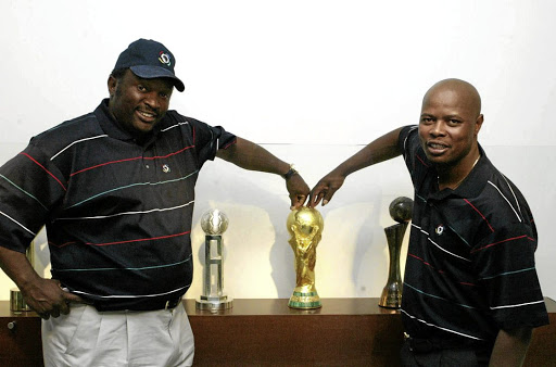Jomo Sono and Phil Masinga with the World Cup trophy during its display at  Fifa House d8d07ac20