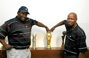 Jomo Sono and Phil Masinga with the World Cup trophy during its   display  at Fifa House in 2010.