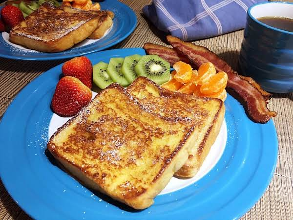 Two French Toast On A Serving Plate Along With Cooked Bacon Slices, Oranges, Kiwifruits And Strawberries.
