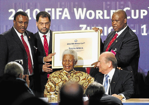 The South African delegation of Irvin Khoza, Danny Jordaan and Nelson Mandela, with Fifa president Sepp Blatter and Molefi Oliphant showing the name of South Africa at the announcement that the country would host the 2010 Soccer World Cup, during an official ceremony in Zurich, Switzerland, on May 15 2004.