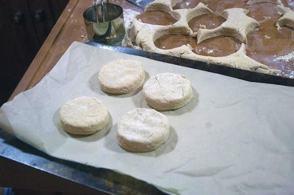 Use a biscuit cutter to cut out the biscuits, and then arrange them on...