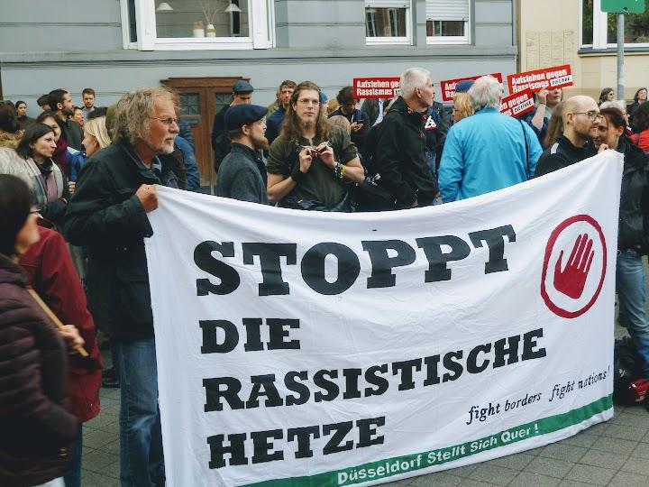 Protestler*innen mit Schildern, Transparent: «Stoppt die rassistische Hetze...».