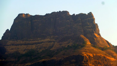 Photo: The Chanderi massif with the dark gash of our route clearly visible in the first [left] quarter of the buttress. The Shivaji monument and flag can also be seen on the summit to the left of the route.