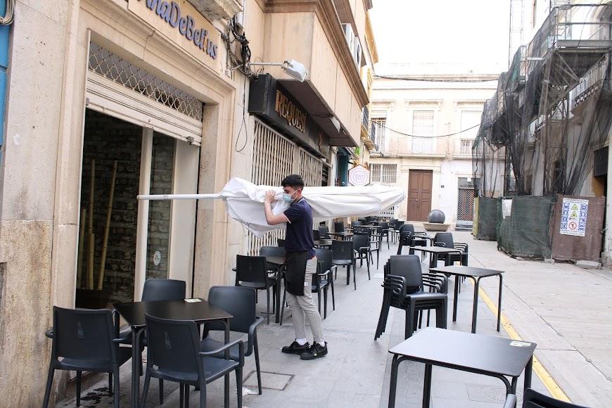 Guardando las sombrillas de la terraza para el cierre.