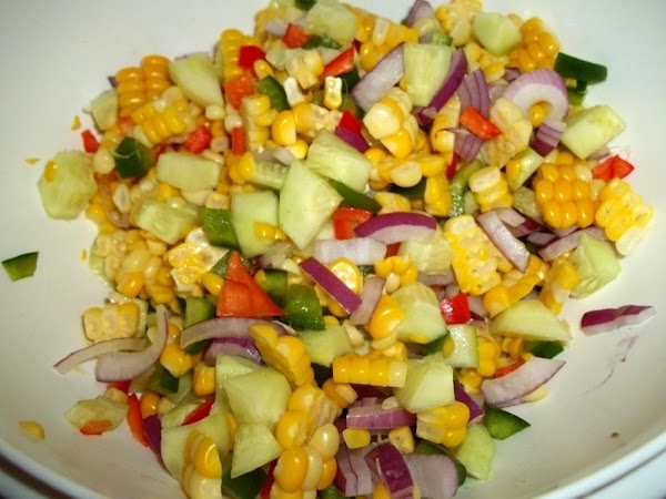 In a medium bowl, add peppers, onions, cucumbers, and corn - toss well.