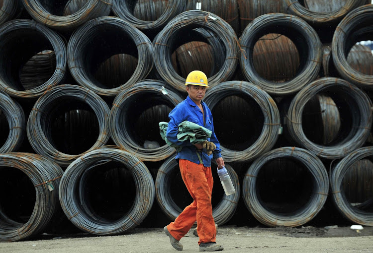 A labourer walks past piles of steel coils at a steel wholesale market in China. Picture: REUTERS