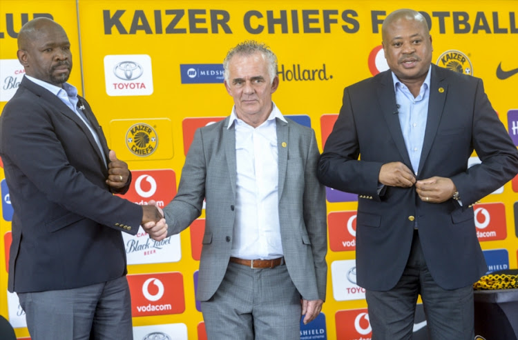Embattled Kaizer Chiefs head coach Steve Komphela shakes hands with newly appointed technical advisor Rob Hutting while the club's football manager Bobby Motaung watches on during a media briefing at Chiefs Village on January 10, 2018 in Johannesburg, South Africa.