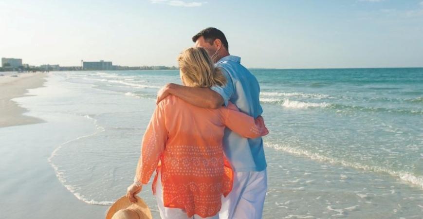 a couple walking along a beach in Sarasota, FL