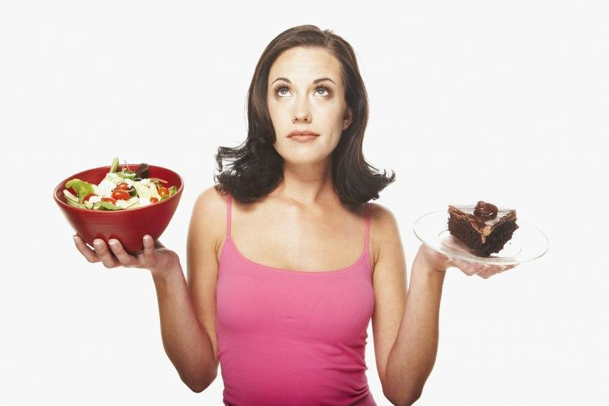 girl holding salad and chocolate cake