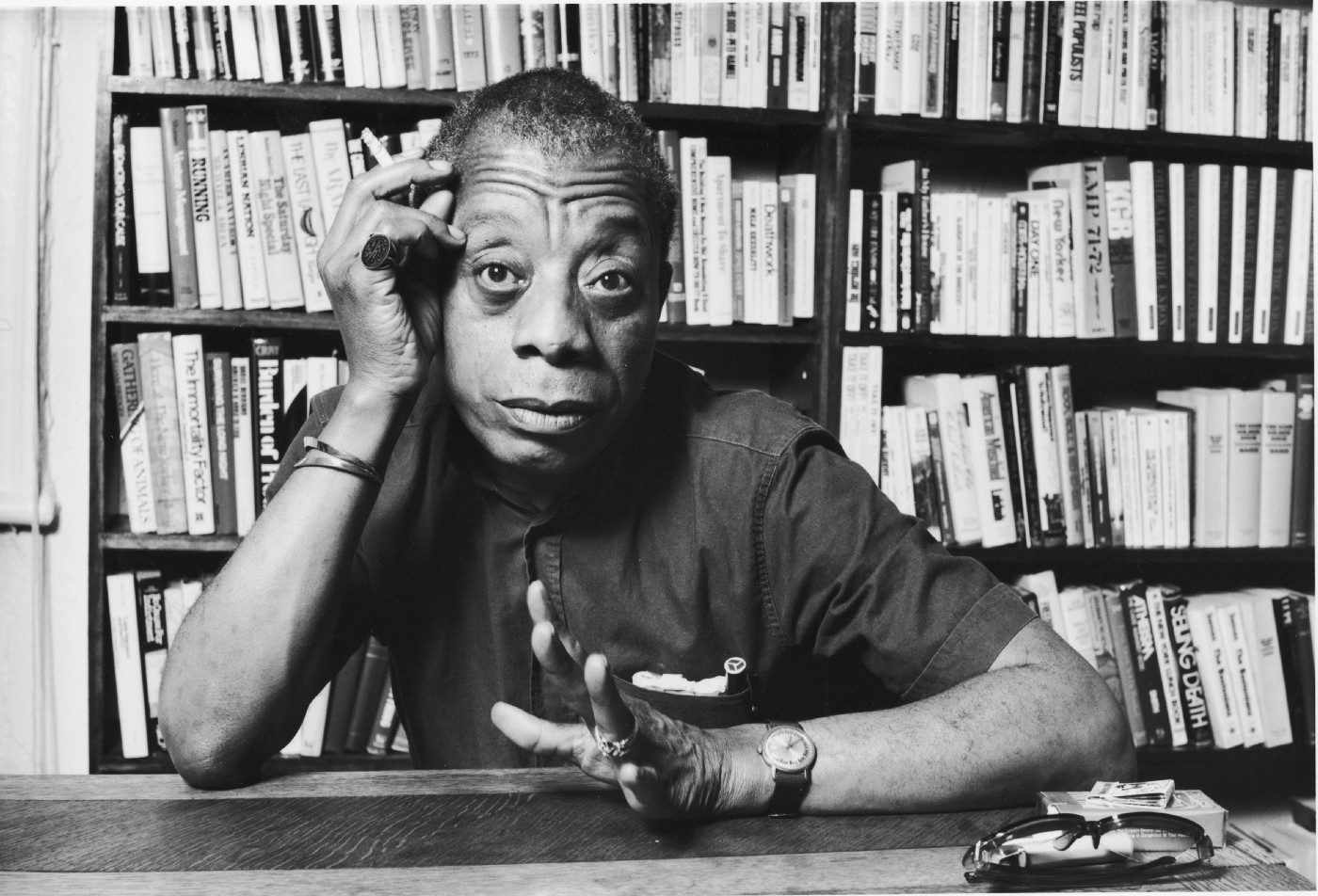 In this black and white image, sitting at a desk of a library with a lit cigarette in right hand, James Baldwin gestures left hand towards the camera.