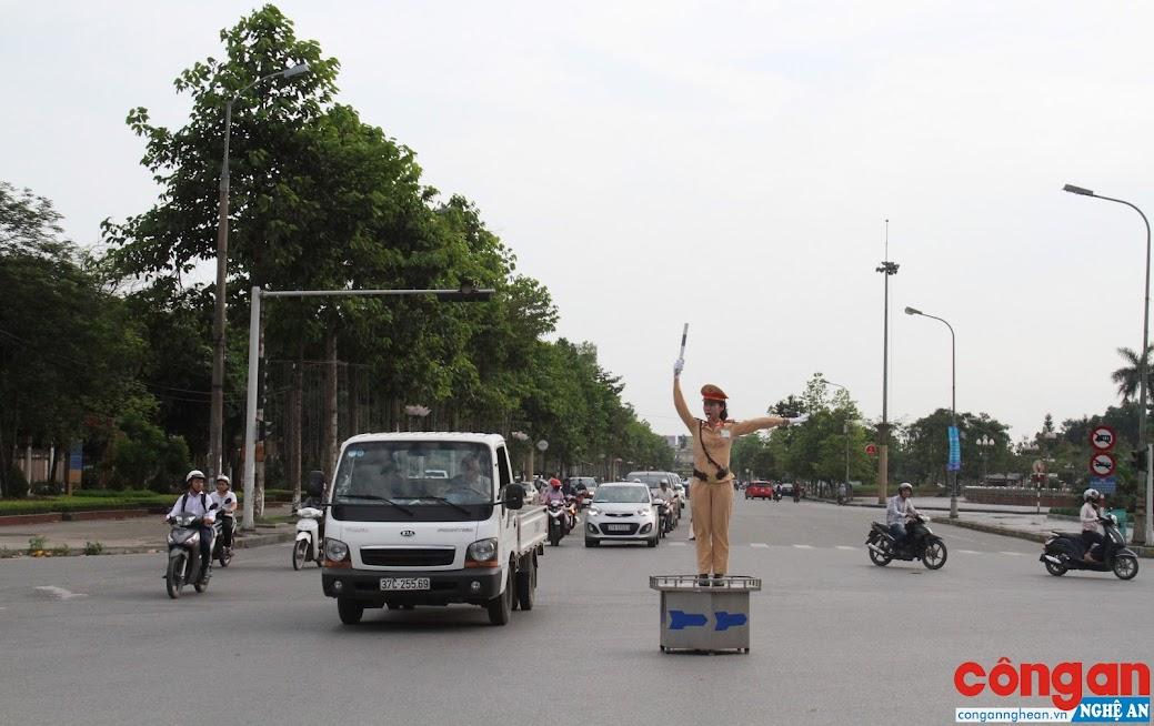 Nữ Cảnh sát giao thông đang chỉ huy, hướng dẫn người tham gia giao thông tại một ngã tư trong thành phố