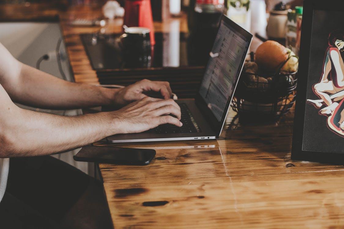 Persona Di Fronte Al Computer Portatile Sul Tavolo Di Legno Marrone
