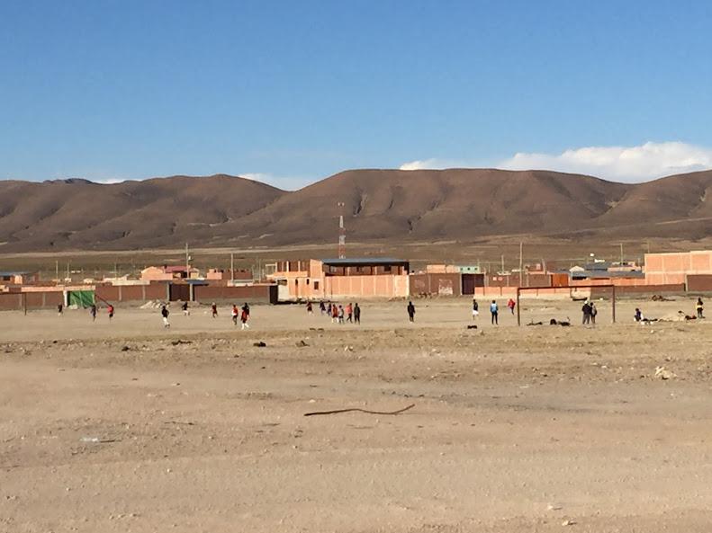 ウユニの広大な大地をバックにサッカーをする地元の子供達