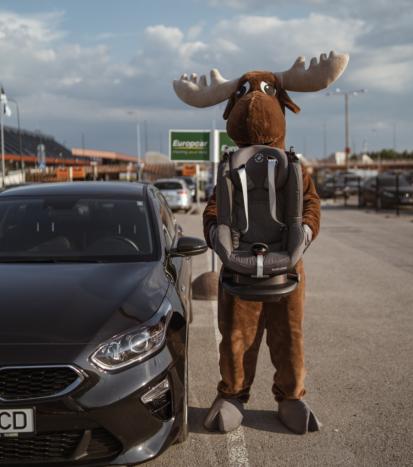 Rental Moose mascot holding child seat, a piece of additional equipment when renting a car, next to Kia Europcar rental car. Rental Moose is a global car rental broker which will help you get the best deal on your next rental car.