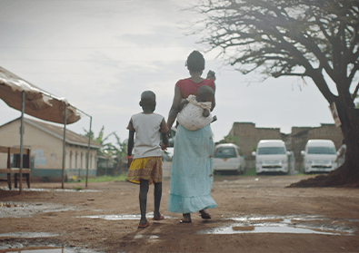 A woman carries her baby on her back and holds her daughter's hands as they walk away along a dirty road.