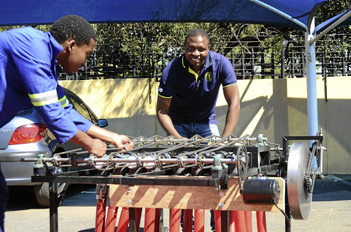 Clement Mokoenene, right, and a member of his team test their new energy harvesting system that can generate electricity enough to light up an RDP house using traffic. / Mduduzi Ndzingi
