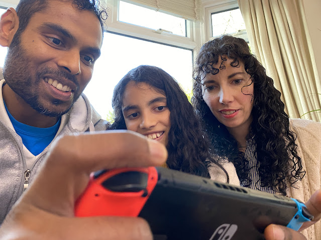 Family of three sitting together. The man is holding a gaming controller and the girl and woman are looking at it too.