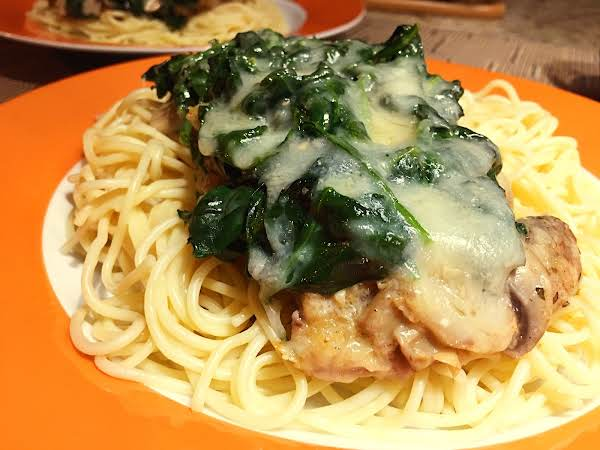 Spaghetti Topped With Veal And Spinach Mixture On An Orange/white Plate.