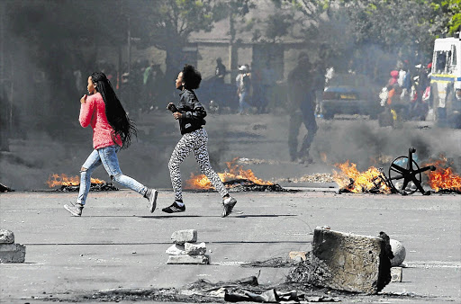 NOT THEIR SCENE: Girls run for cover after Langa residents barricaded a road during a service delivery protest yesterday.