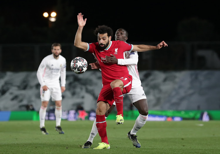 Mohamed Salah of Liverpool battles for possession with Ferland Mendy of Real Madrid during the UEFA Champions League quarterfinal at Estadio Alfredo Di Stefano on April 6, 2021 in Madrid