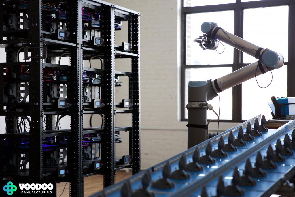 Кластер из девяти 3D-принтеров, обслуживаемых роботизированной рукой. Конвейерная лента трехмерных печатных объектов на пластинах справа