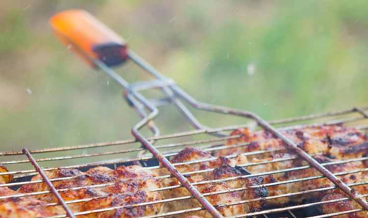 A hinged braai grid makes short work of turning a load of chicken pieces.