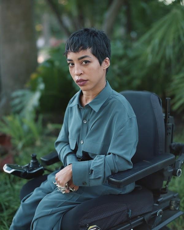 Jillian Mercado, founder of Disabled Black Creatives in their wheelchair wearing a teal silk shirt.