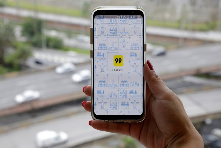 A photo illustration shows the 99 app on a mobile telephone, as it is held up for a posed photograph in Sao Paulo, Brazil on January 3, 2018. Picture: REUTERS/PAULO WHITAKER