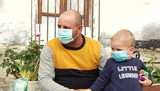 Padre e hijo, con sus mascarillas, en un banco de Velefique.