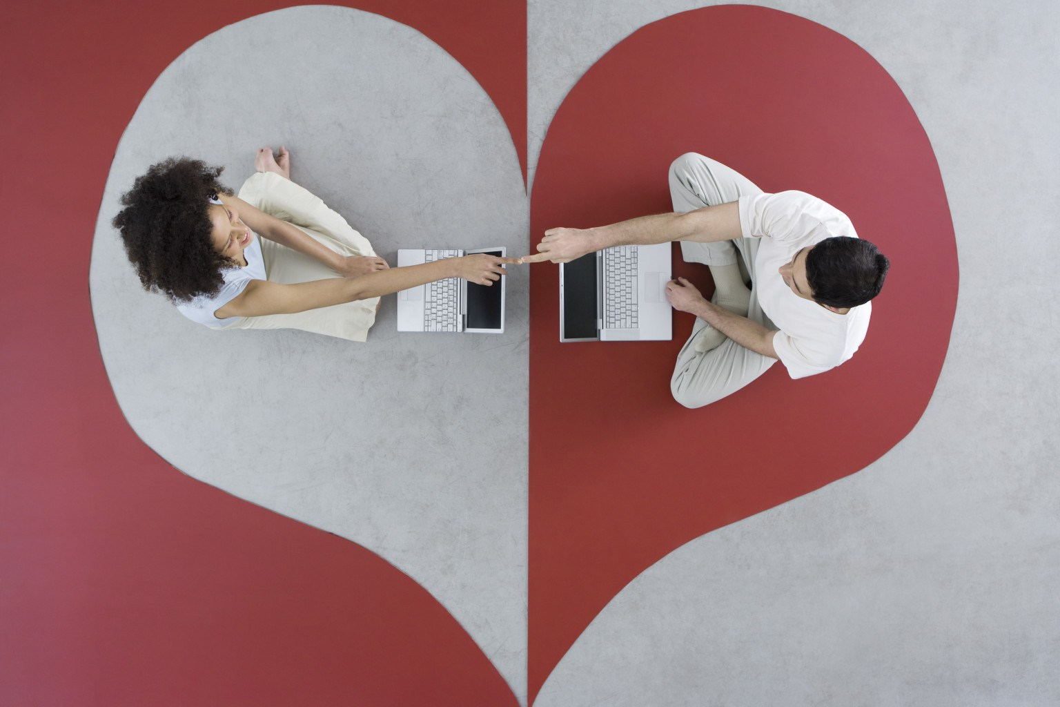 Couple sitting face to face with laptop computers on heart shape, touching fingers, overhead view