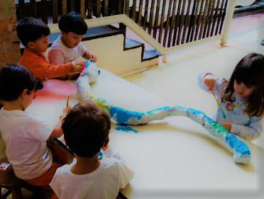A imagem mostra quatro crianças ao redor de uma mesa branca, pintando uma grande lagarta com tinta azul.