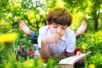 Boy about 8 years old reading outdoors