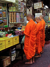 Photo: monks with alms bowl outside a shop in the alley in Chinatown