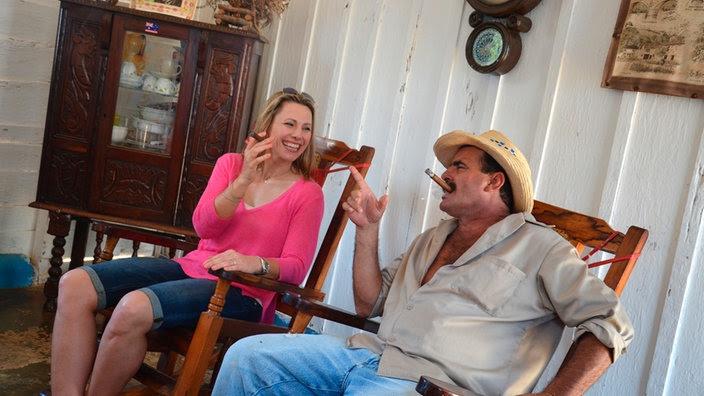 Zwei Zigarren rauchende Menschen in Schaukelstühlen.