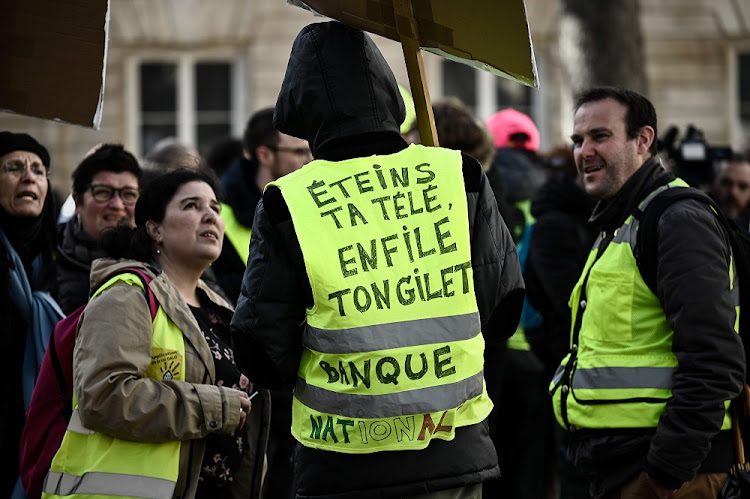 A protester wears a yellow vest reading 'Turn off your TV, put on your vest' during a demonstration in Paris, France, March 13 2019. Picture: PHILLIPPE LOPEZ/AFP