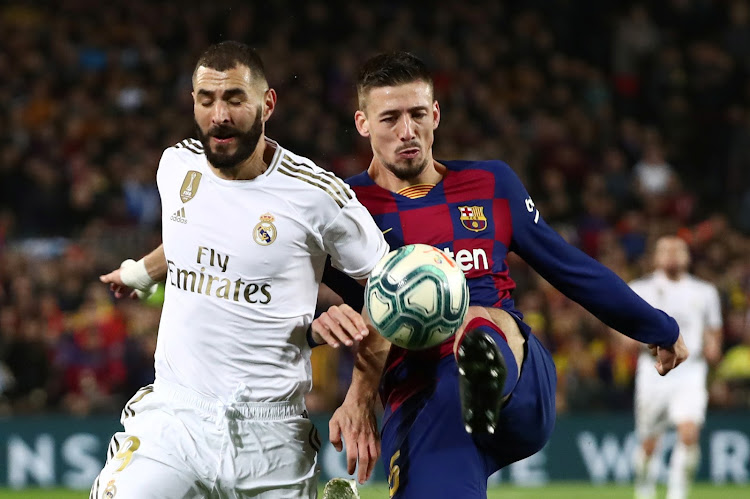 Real Madrid's Karim Benzema in action with Barcelona's Clement Lenglet in a past match