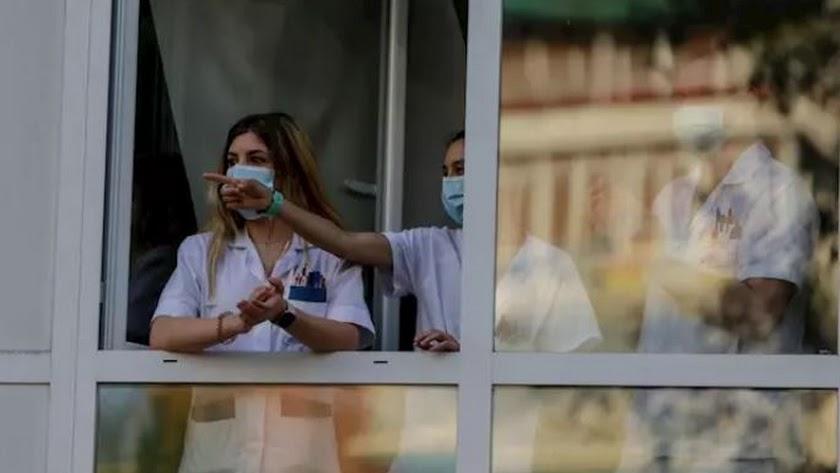Sanitarios asomados a la ventana de un hospital.