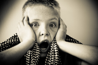 Photo: Portrait of scared and screaming young boy