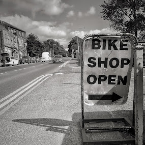 The Bike Shop by Brian Egerton - City,  Street & Park  Street Scenes ( shop, bikes, blackandwhite, road, street, sign, clouds, black and white, bike )