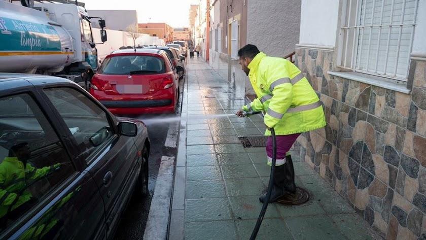 Trabajador baldeando una calle de la ciudad de Almería