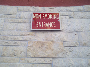 Photo: I was pleased to see this sign as I walked out of the mall, since going in and out of work is a real pain when a pack of smokers is out there.  The lady standing among the bushes a good distance away looked less thrilled as she puffed on her cigarette.