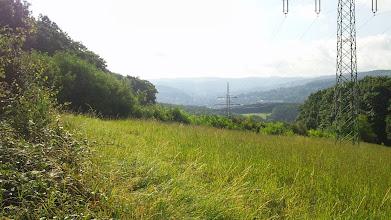 Photo: Teil des unteren Volmetals mit dem Stadtzentum von Hagen im Morgendunst vor der Philippshöhe (links) und dem Postkopf (rechts von dem hinteren Masten); es folgt zwischen den Masten das Tal des Kuhler Baches (Kuhlebachtal). Aufgenommen am Wanderweg mit der Raute (,Vorfahrtschild') als Kennung. Hinter dem Postkopf das Tal der Ennepe, welche ,im Loch' hinten (aber vor Delstern!) in die Volme mündet (Bahnhofsgegend).