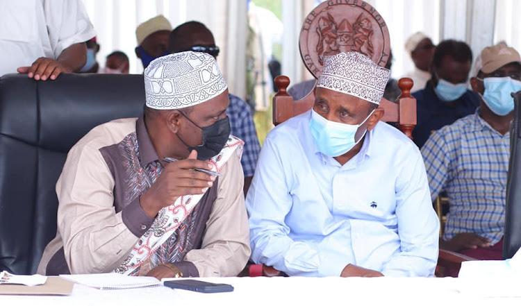 Treasury CS Ukur Yatani has a word with Garissa governor AlI Korane during a prayer meeting for the late Senator Yusuf Haji in Masalani town, Ijara constituency.