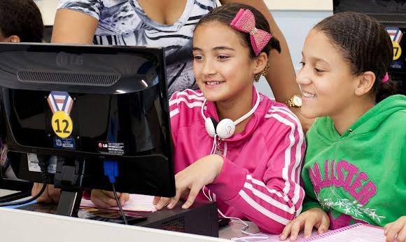 Dos jóvenes brasileños y un instructor miran una computadora durante una lección digital.
