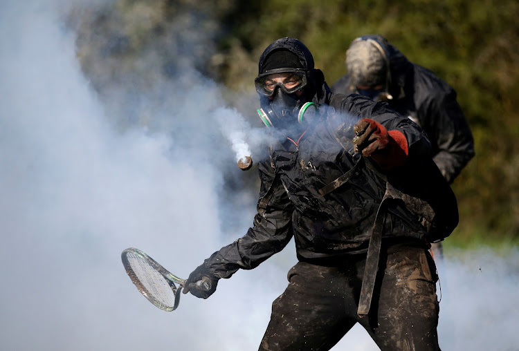 A protester uses a tennis racquet to hit a tear gas canister during the evacuation operation by French gendarmes in the zoned ZAD (Deferred Development Zone) at Notre-Dame-des-Landes.