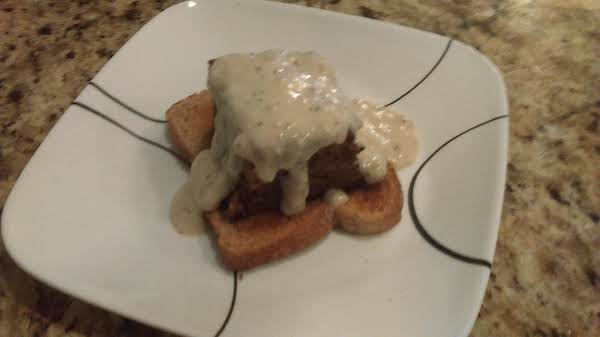 Open Face Honey Moist Meatloaf Topped With Sausage Gravy.